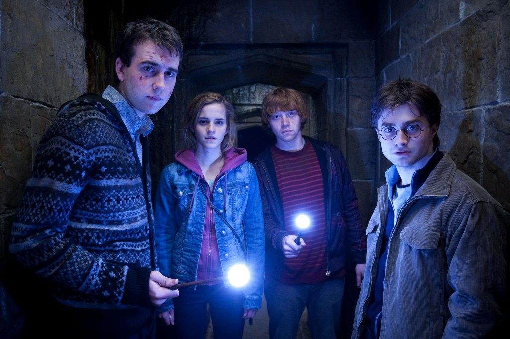 Scéna z filmu HP a Relikvie Smrti. V tmavé chodbě je vlevo Neville se šrámy v obličeji a ve vzorovaném svetru, s napřaženou svítící hůlkou. Vedle Hermiona v růžovém a džinové bundě. Vedle ní Ron v červeno-oranžově pruhovaném tričku a hnědou mikinou, s napřaženou rozsvícenou hůlkou. Úplně vpravo Harry v okrovém manšestrovém saku. Všichni se dívají jedním směrem napravo od diváka.