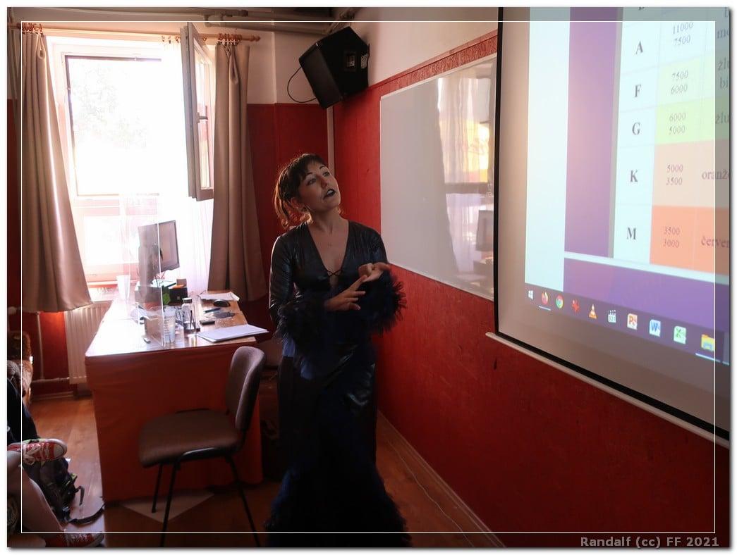 Na fotografii je cosplayerka v kostýmu Nagini před interaktivní tabulí, na kterou se dívá. Za ní je stůl s počítačem, papíry a dalšími pomůckami. Za počítačem je otevřené okno se záclonami a okrovými závěsy.
