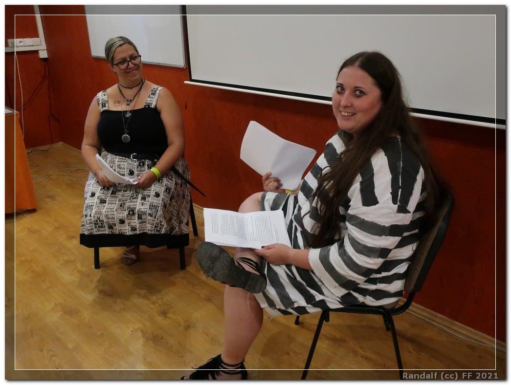 Na fotografii jsou dvě sedící ženy před interaktivní tabulí. Více vzadu je usměvavá žena v šatech, jejich živůtek je černý a sukně je z látky, na níž jsou listy z Denního věštce. V rukách drží papíry. Stejně tak druhá žena sedící blíže k divákovi, která má na sobě azkabanský mundúr. Pravou nohu má přes levou a v obou rukách drží papíry. Usmívá se přímo na diváka.