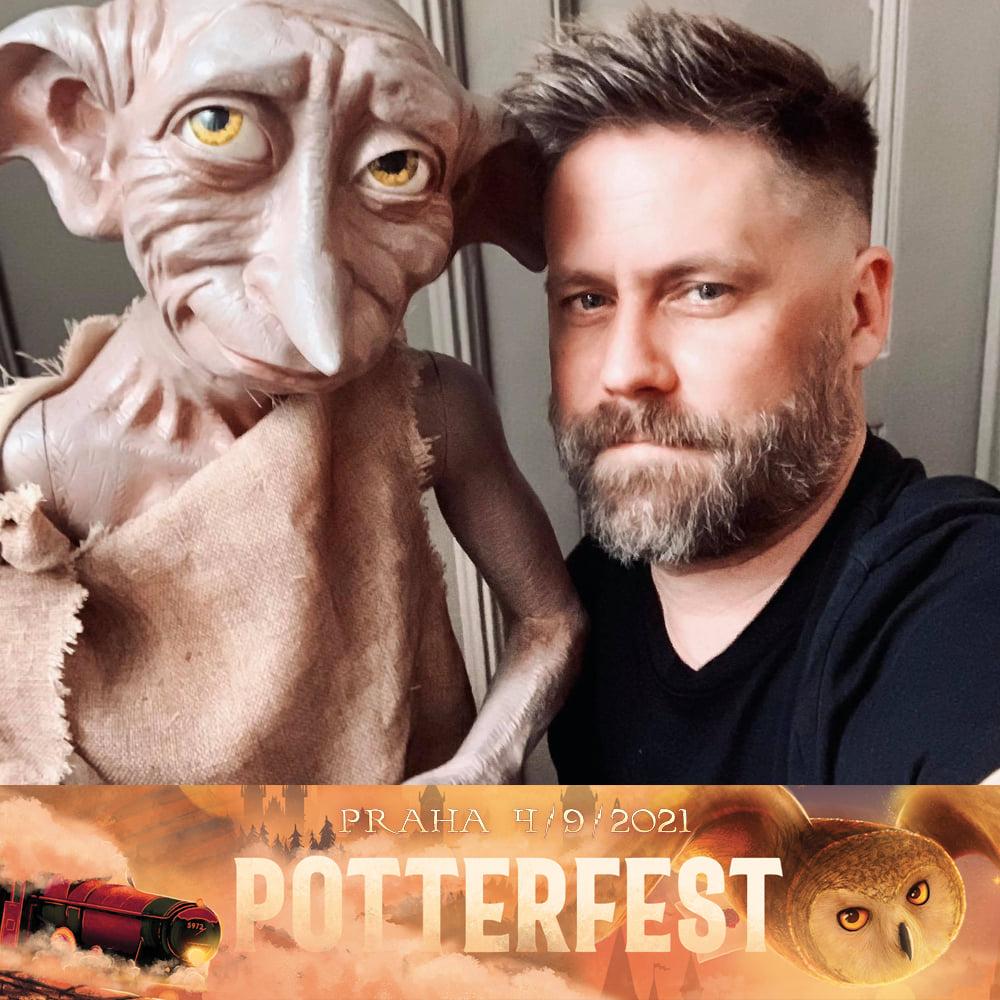 Na fotografii je zsrostlý muž s nagelovanými vlasy a v čeném tričku. Vlevo vedle něj je velká figurína Dobbyho. On se dívá vzhůru a muž na diváka. Pod fotografií je logo Potterfestu.