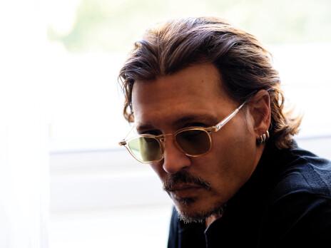 Fotografie Johnnyho, na které se dívá přes obroučky slunečních brýlí do objektivu. Vlasy má sčesané dozadu, hlavu natočenou lehce doleva. Nijak se neusmívá, má spíše vážnější výraz.