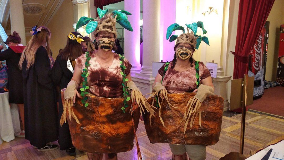 Fotografie z Potterfestu 2021 s cosplayerkami v roli dvou mandragor. Z hlavy jim koukají listy, mají roušky s přidělanými rádoby ústy a na kšandách mají zavěšený kolem těla obří květináč.