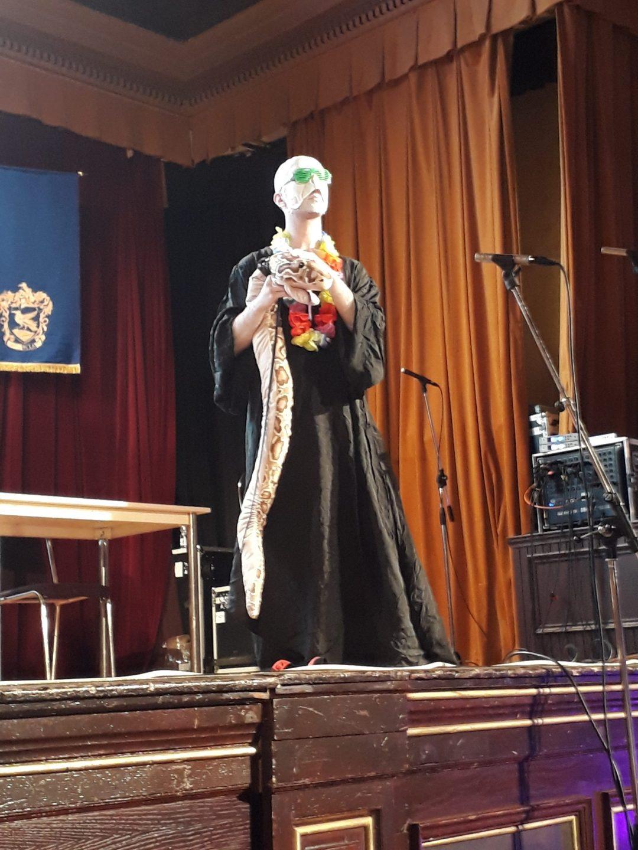 """Fotografie z Potterfestu 2021 ze závěrečného divadla """"Kouzelníci zájezdu"""". Na fotografii vidíme Voldemorta s Nagini a havajským květinovým věncem okolo krku."""
