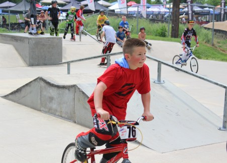 Children bicycle and ride scooters outdoors at the skate park of Memorial Park in Pottstown.