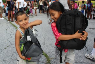 Victor Hernandez, 4, and Quetzalli Cruz, 7, show off their brand new book bags filled with school supplies. Children received the bags during a Back to School Community Blockbuster at the Ricketts Center in Pottstown Saturday.