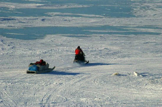 Snowmobile and qamutik heading out for hunting or fishing