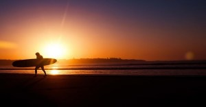Por do sol com surfista e prancha header 960