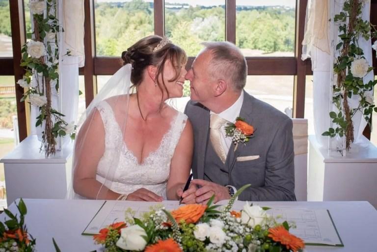 Bride and groom sign the wedding register at Cumberwell Park wedding venue