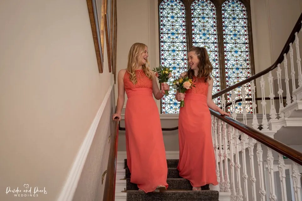 Bridesmaids walk past stained glass window at Eastwood Park