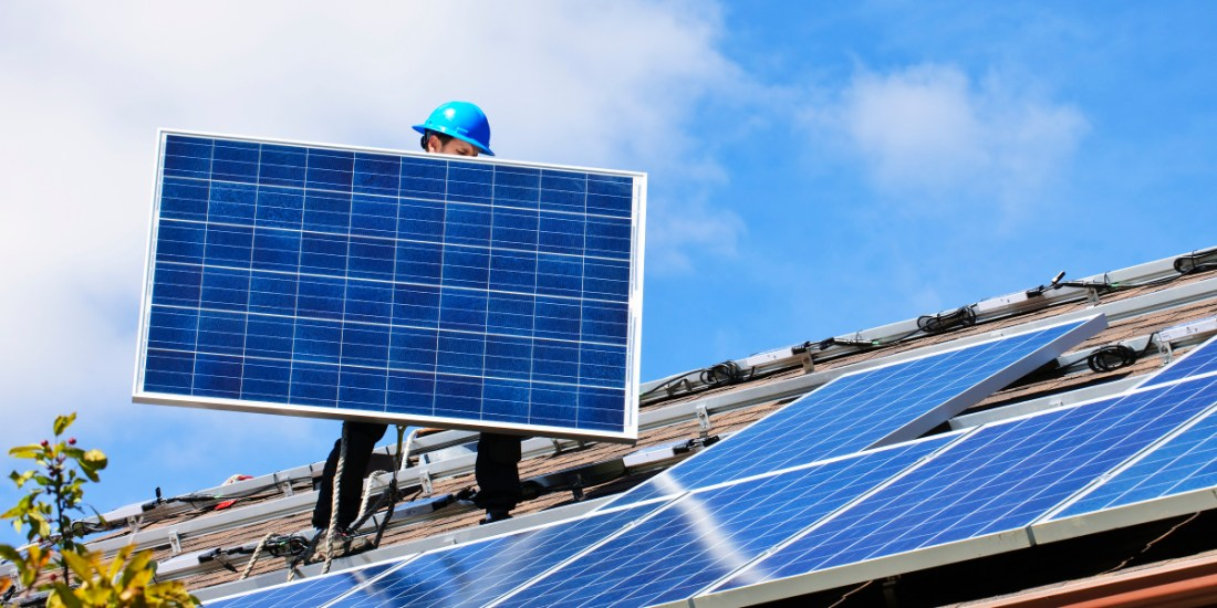 Man carrying solar panel on roof