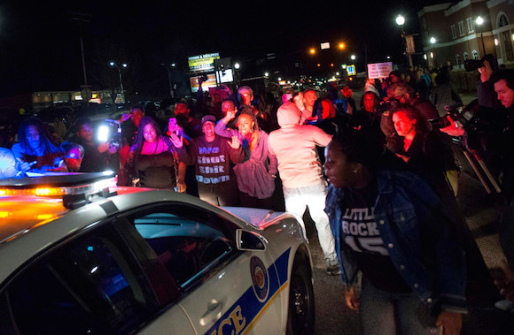 Protestors block a police vehicle from entering the City of Ferguson Police Department and Municipal Court parking lot in Ferguson Missouri