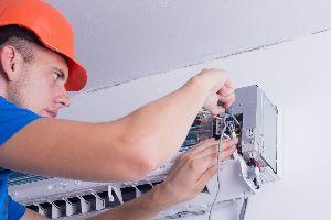 man in orange hard hard with tools fixing a mini-split