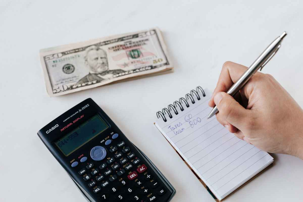 hand writing on notepad with calculator and $50 dollar bills
