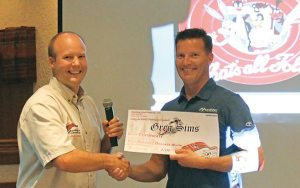 Adam Wood from Starting Line Products presents Marshall's Greg Simms with the top salesman award.