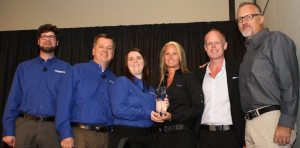 GM Gina Marra accepts the No. 1 dealer trophy from PSB editors (from left) Tom Kaiser, Dave McMahon and Liz Keener.