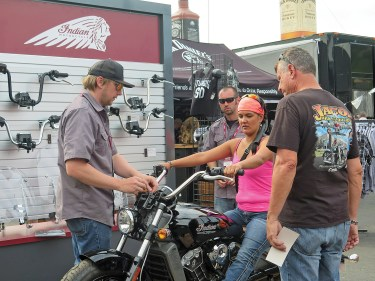 An Indian Motorcycle staffer assists a rider in getting fit for handlebars on the Indian Scout at the Polaris booth on Lazelle Street. Polaris doubled the size of its display from 2014 to 2015.