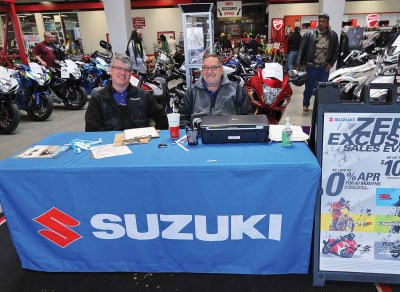  Ron Myers and Bill Scharff from event sponsor Suzuki signing folks up for free Suzuki demo rides. Note the super sales promotion for Suzukis purchased during and after the event.