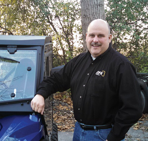 Mike Kelly, vice president and general manager of DFK Cabs, stands alongside DFK's new cab for the Yamaha Wolverine.