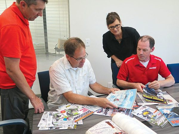 (From left) Snow Goer national account manager Mark Rosacker, editor and publisher John Prusak, art director Becca Hudson and managing editor Andy Swanson look over the past issues of the magazine.