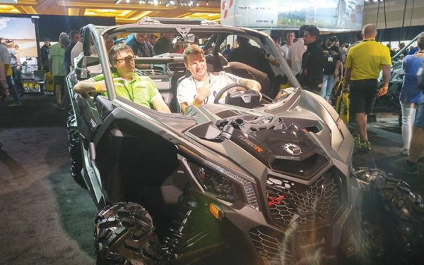 A couple dealers pose for a photo inside a Maverick X3 at Club BRP in Orlando.