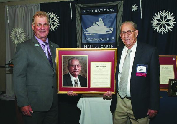 Jerry Schmier, right, accepts his International Snowmobile Hall of Fame award.