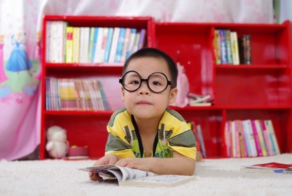 Asian boy with large glasses reading a book