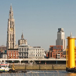 Баржу с нефтеперерабатывающими колонками перегоняют по Шельде на фоне собора Антверпена и здания банка KBC