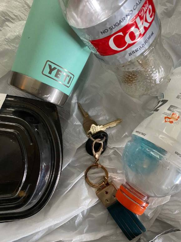 A trash bag containing a Yeti drinks container, a plastic Coke bottle and a set of car keys