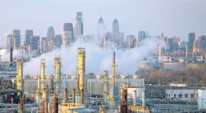 Philadelphia skyline on a clear day. White steam billows up from the refinery below, major pieces of oil refinery process equipment become visible.