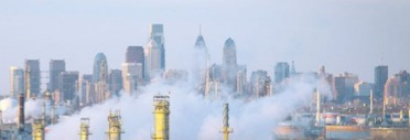 Philadelphia skyline on a clear day. White steam billows up from the refinery below, tops of process equipment become visible.