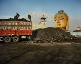 An unfinished Buddha head peers from a coal yard in northern China.