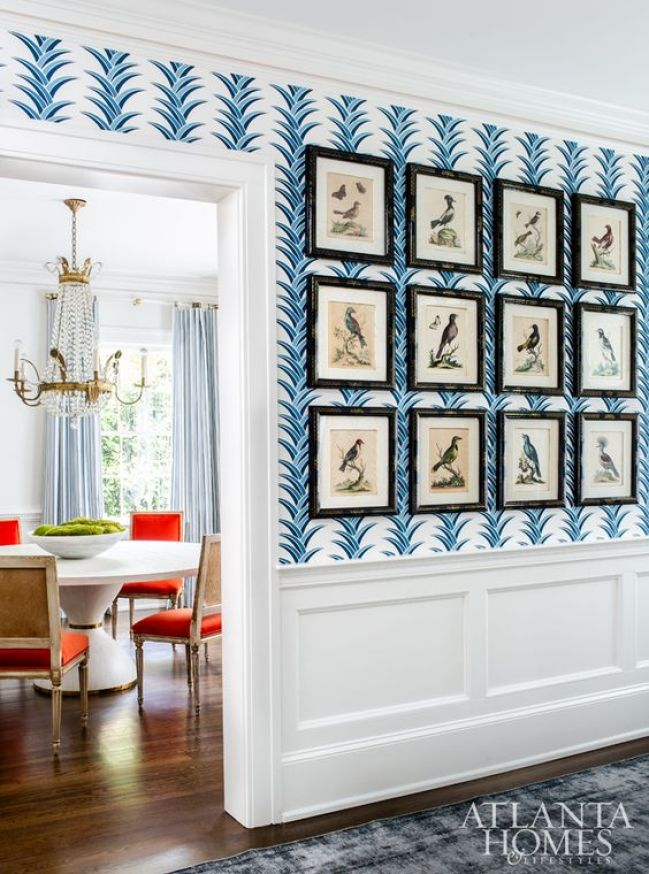 In a traditional Dutch Colonial revival hallway, we can see bright orange upholstered vintage chairs in a dining room with an elaborate chandelier hanging over a modern dining dining table. The hallway has blue wallpaper with a curved pattern that mimics the curves of the chandelier. There's white wainscoting on the lower portion of the wallpaper wall.