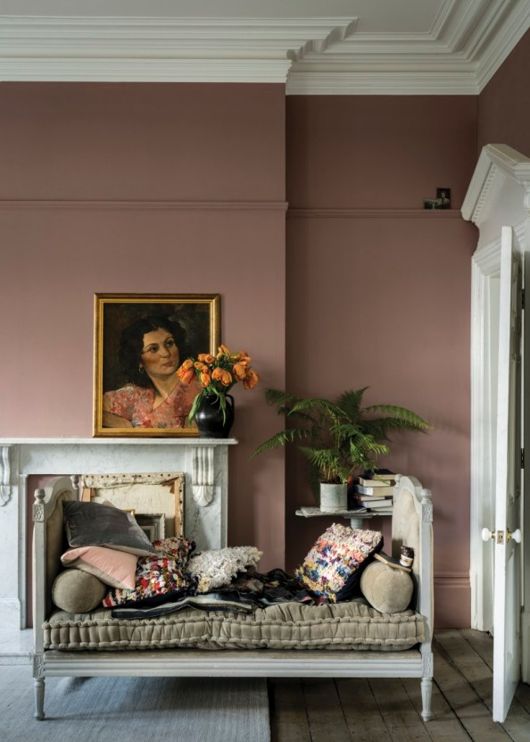 In this transitional living room, a dusty pink wall color plays off of the grey stonework in an old fireplace, with a framed vintage portrait of a woman on the mantle.