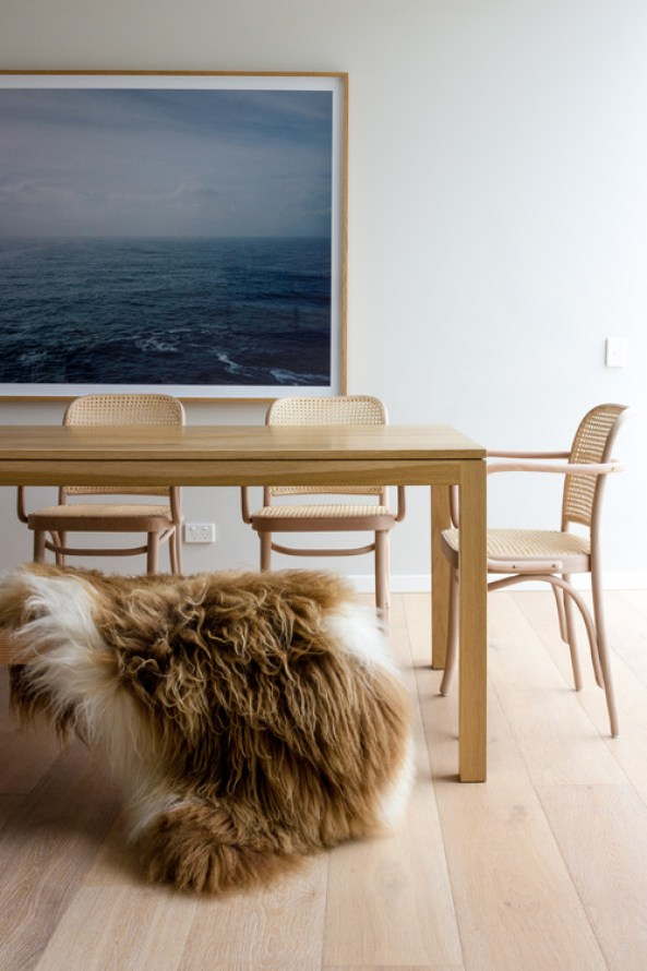 Cozy, 'California Cool' boho dining room with a medium sheepskin pelt draped over the dining bench: get the look on a budget