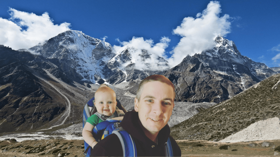 Dad carrying baby in backpack in front of Mount Everest.