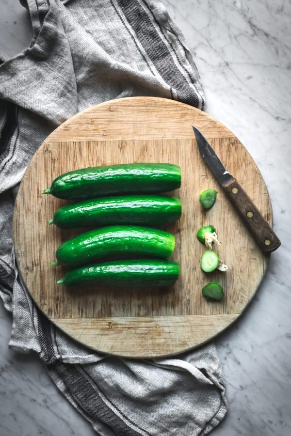 Preparing cucumbers for fermented pickles ~ Four cucumbers on a cutting board with blossom end removed.
