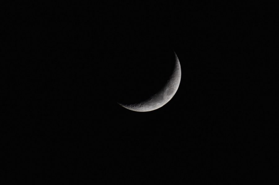 A slight crescent moon shines against a dark black night sky.
