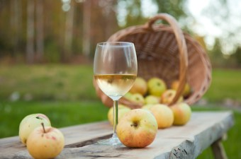 Glass of apple wine on a table in front of a basket of apples