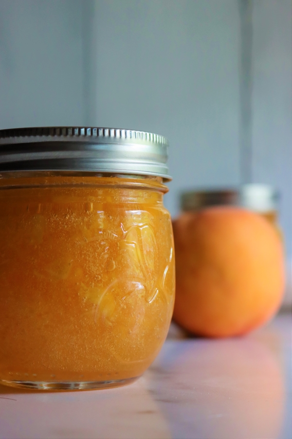 Homemade peach jam has a beautiful orange color because the peaches were treated with lemon juice as they were cut to prevent browning.