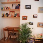 A reading or working nook, gallery wall, and board games in the lounge at Kabas Hostel in Antwerp, Belgium.