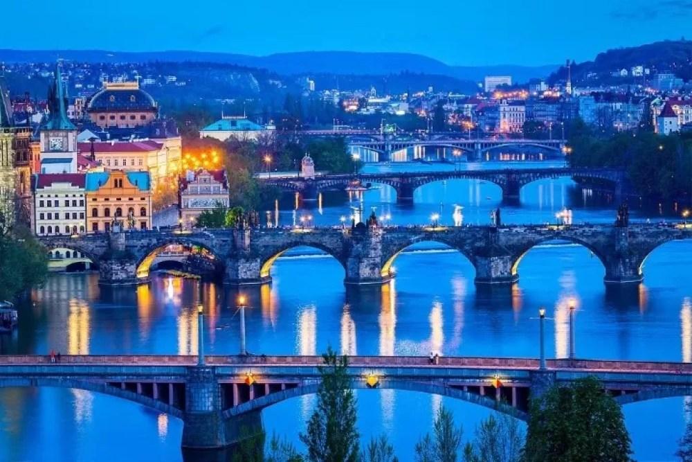 Travel Prague concept background - elevated view of bridges over Vltava river from Letna Park. Prague, Czech Republic in twilight