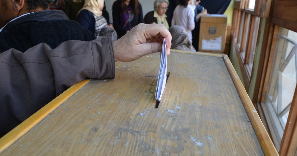 hand placing election ballot into ballot box