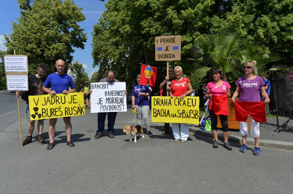 Protesters brandishing signs and red shorts gather outside Lany castle against Babis and zeman