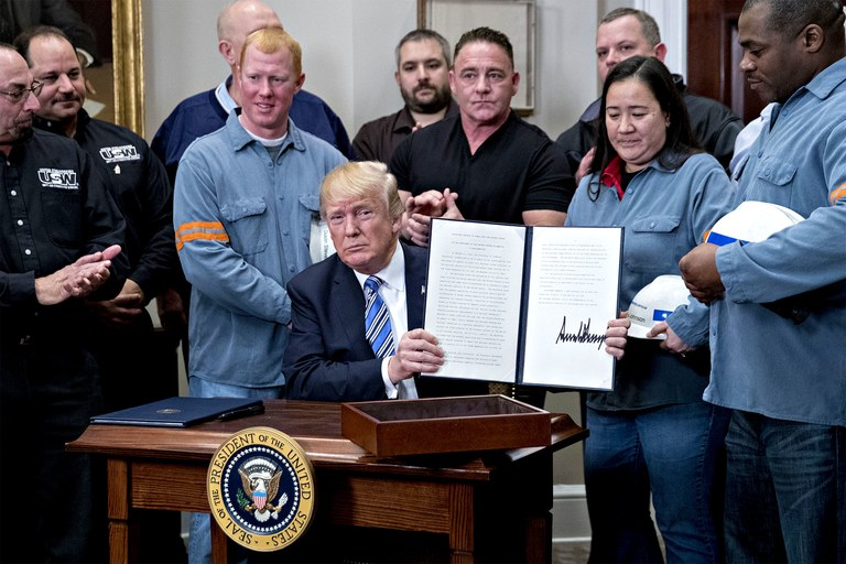 Donald Trump SIgns into Law 25% duties on steel imports surrounded by domestic steel workers