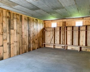 Photo of the inside of the Grooms Suite. The walls are covered with wood panels, there are built in storage cubbies, the ceiling is made of refurbished pieces from the original structure, the ground is cement.