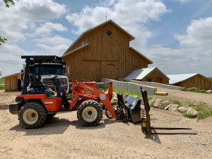 Prairie Bells Barn with a large tractor and semi truck outside during construction.