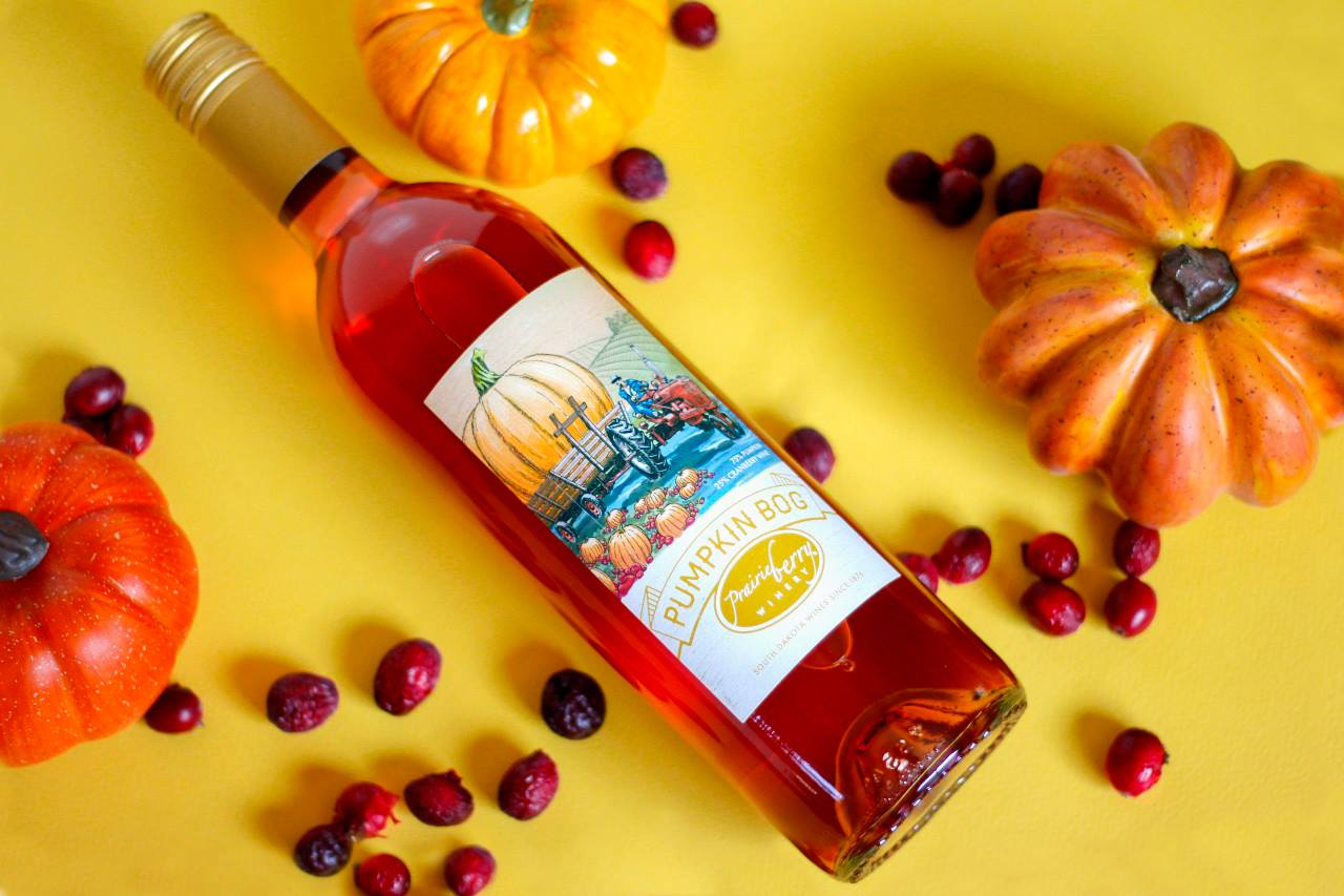 A bottle of Pumpkin Bog wine by Prairie Berry Winery against a festive fall setting.