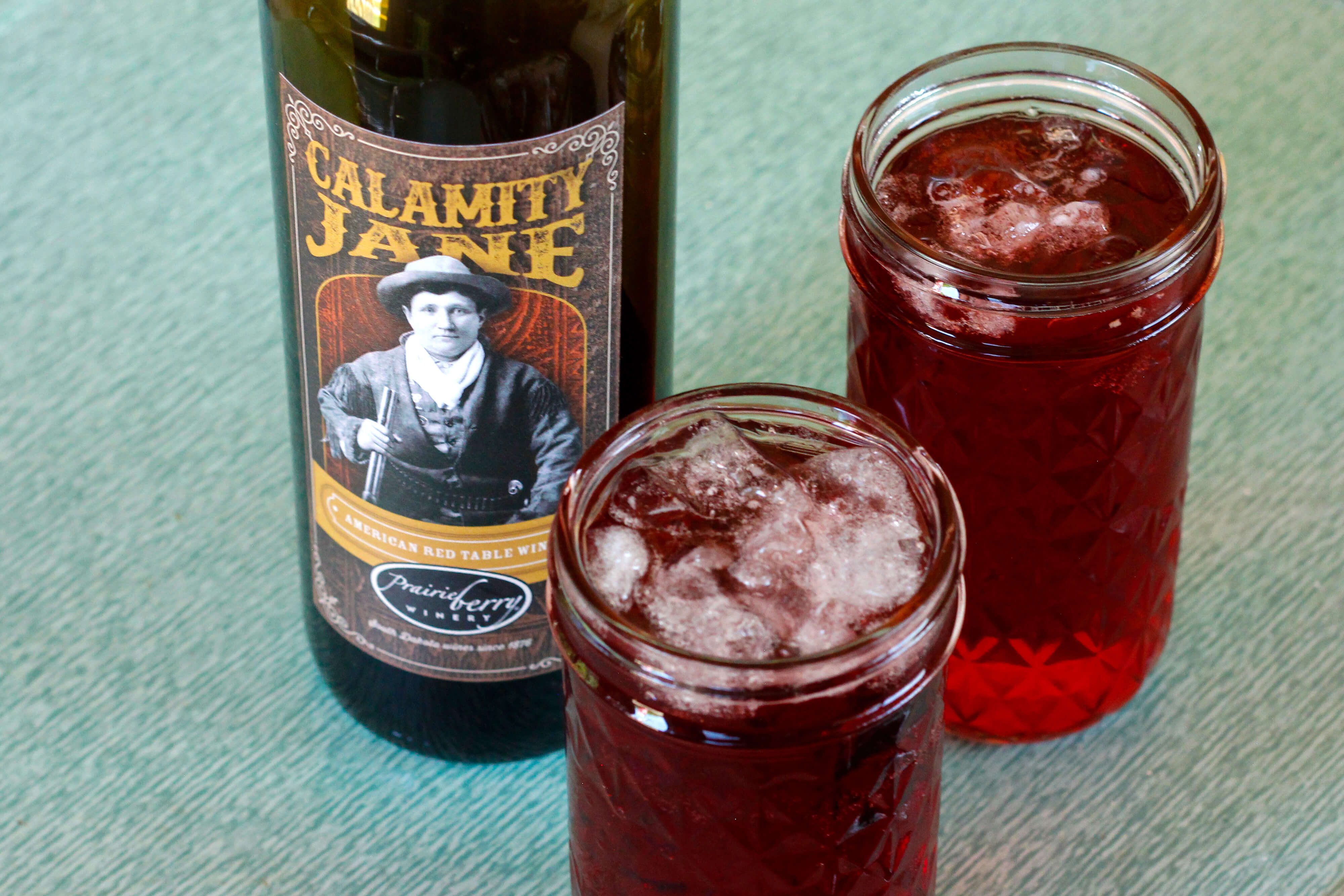 Two glasses of Calamity Jane Spritzer with a bottle of Calamity Jane wine.