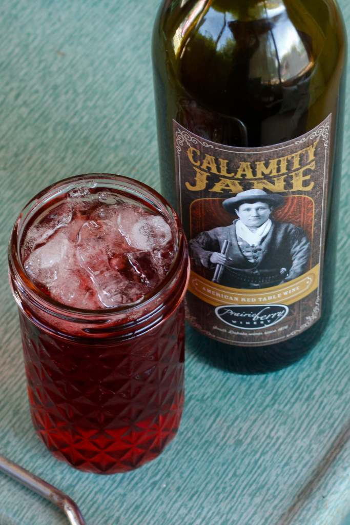 A glass of Calamity Jane Spritzer with a bottle of Calamity Jane wine.