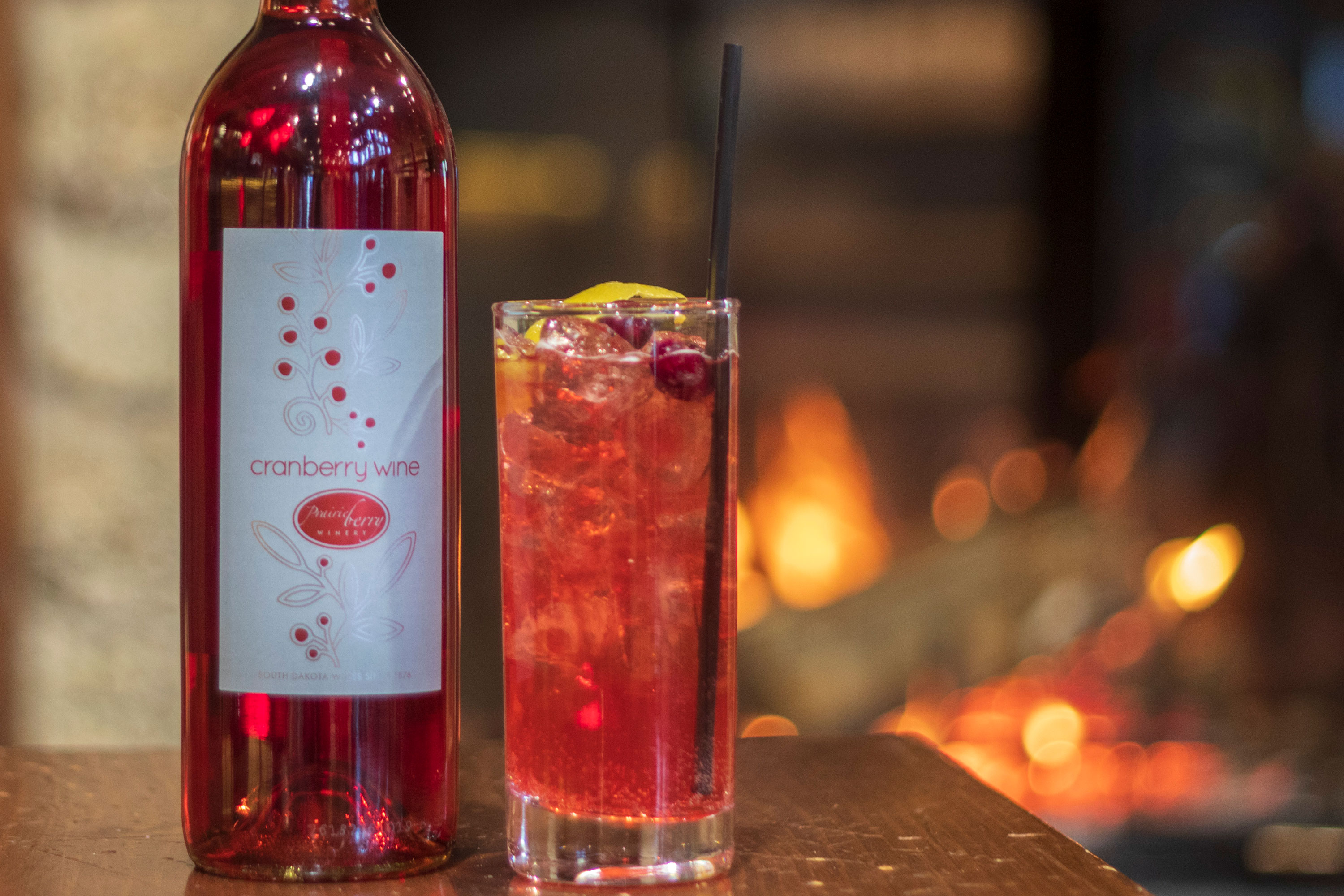 A glass of Cinnamon Cranberry Spritzer with Cranberry wine in front of a fireplace.